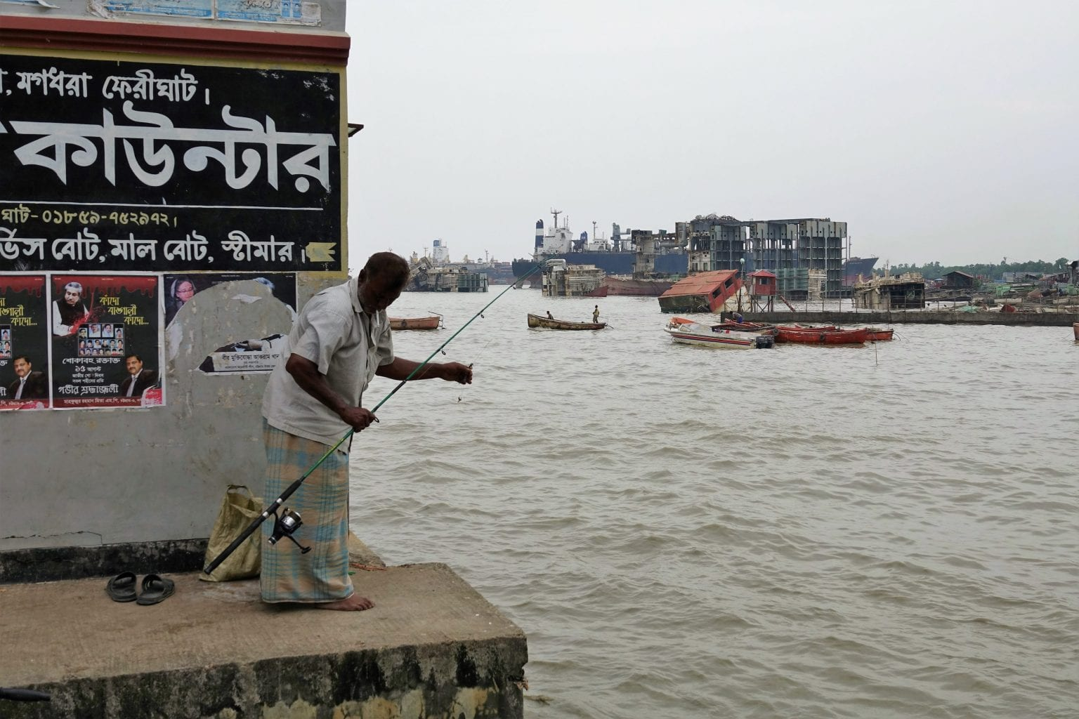 En mand fisker ved havnen i Chittagong. I baggrunden ses de store vragdele fra skibsophugningen. Foto: S. Rahman/Danwatch
