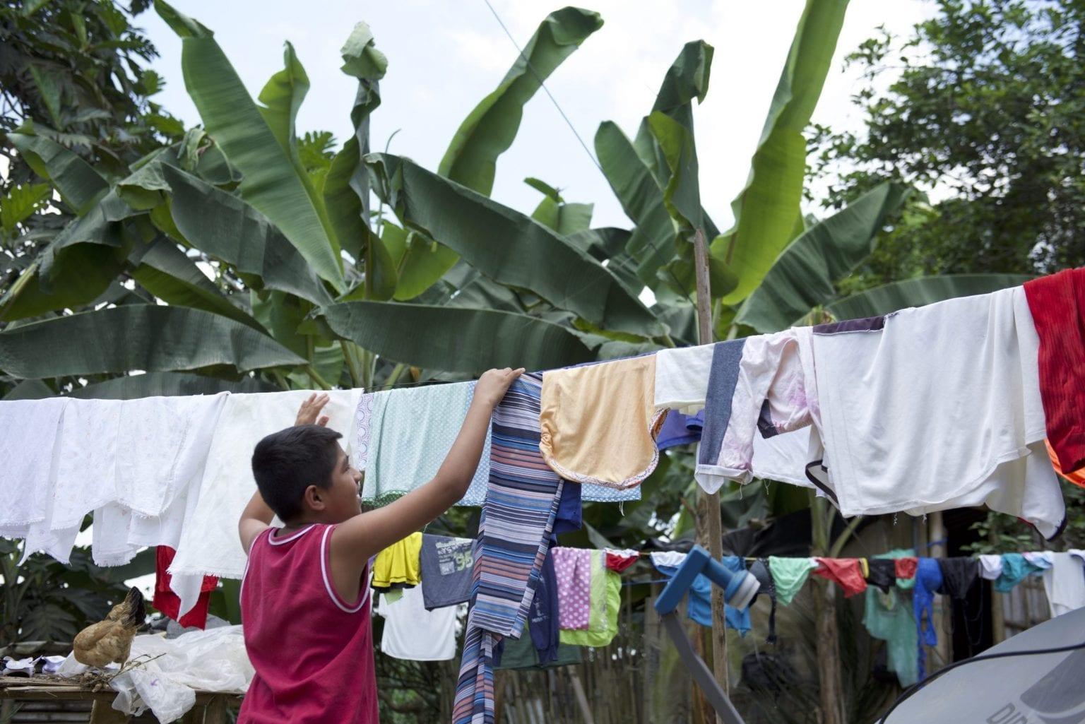 En dreng i landsbyen er omringet af banantræer. Pesticiderne påvirker både arbejdernes sundhed og befolkningen, der lever i banan-områderne.