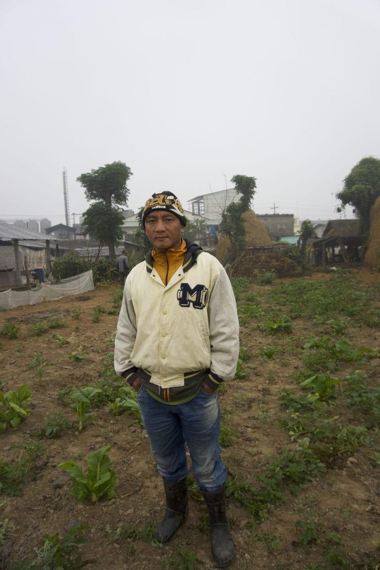 """Rohit Pulami (40) er vokset op i et hus nede ved Narayani-flodens bred, der hvor Carlsbergs bryggeri i Nepal ligger. I dag bor han lige uden for bryggeriets område, hvor han dyrker grøntsager, der brødføder familien.   """"Jeg ved ikke, om hosten er på grund af soden. Men soden er i luften, og den er vi jo nødt til at indånde"""", siger han, mens han går rundt og peger på de sorte partikler, der ligger på majs- og kartoffelplanterne.   Han lægger to fingre om halsen, når han fortæller om sine åndedrætsproblemer.  """"Det er specielt om morgenen, at jeg får hosteanfald. Det føles, som om halsen ikke er åben""""."""