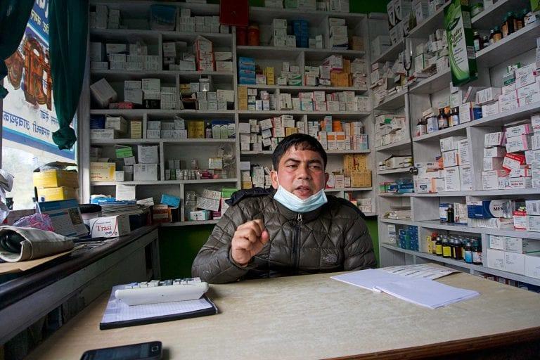 """Hari Dutta Subedi er apoteker, og han udgør det primære sundhedstilbud for småbønderne i Pitaunji, og andre omkringliggende landsbyer.    Patienterne fra Pitaunji kommer ofte med sviende øjne, fortæller han.    """"Fra Pitaunji kommer der mange med øje-problemer, de har røde og rindende øjne, der svier og er irriterede"""".   Han har arbejdet i den lille sundhedsklinik i 15-16 år. Øjenproblemerne i Pitaunji startede for 4-5 år siden.    """"Dem der kommer, siger, at der er en fabrik der afbrænder risskaller, og at det er derfor der er meget støv i luften"""", siger han.   Det varierer hvor mange øjenpatienter der kommer fra Pitaunji, når det er slemt kommer der 25-30 patienter om måneden, anslår apotekeren.   Han giver patienterne øjendråber, og når støvkorn sider fast på øjets pupil sender han dem videre til et øjehospital i den nærmeste by, fortæller Subedi."""