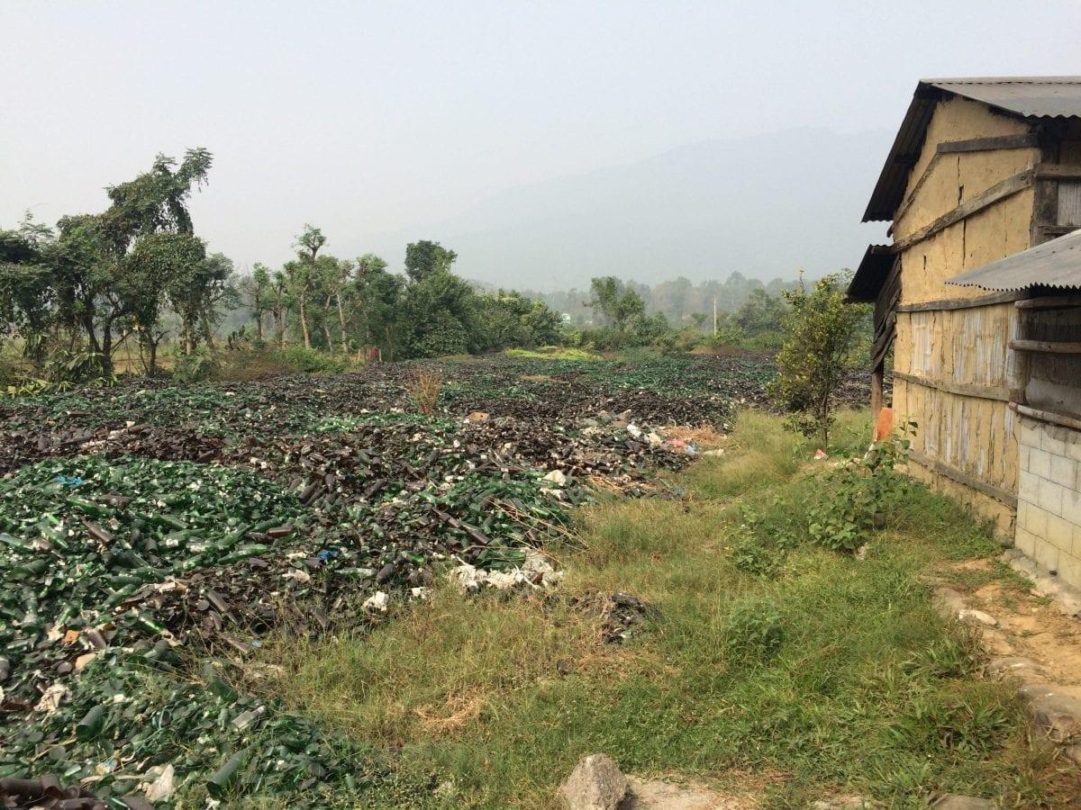 Lokale indbyggere fortæller, at bryggeriet lejer jordstykker i landsbyen, som de bruger til at dumpe affald som ødelagte ølflasker og affaldsække. Foto: Privat, taget af lokale, 2015