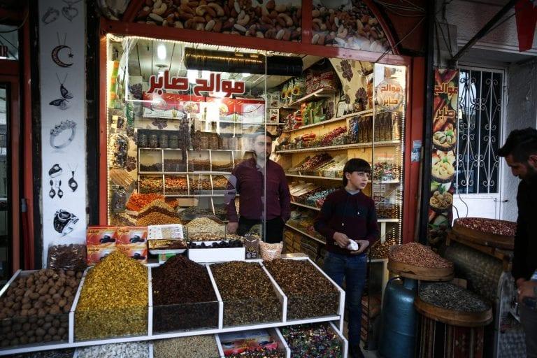 """""""Hvis der ikke havde været en mur, ville de have krydset grænsen. Der er mennesker der dør på den anden side af grænsen, men de kan ikke komme over"""", siger Mohammed Erravi (30), som med hjælp af sin 13-årige syriske assistent driver en lille butik med nødder og tørret frugt på tyrkisk side af grænsemuren. Mohammed Erravi forlod krigen i Aleppo for seks år siden. Foto: Maya Hautefeuille"""