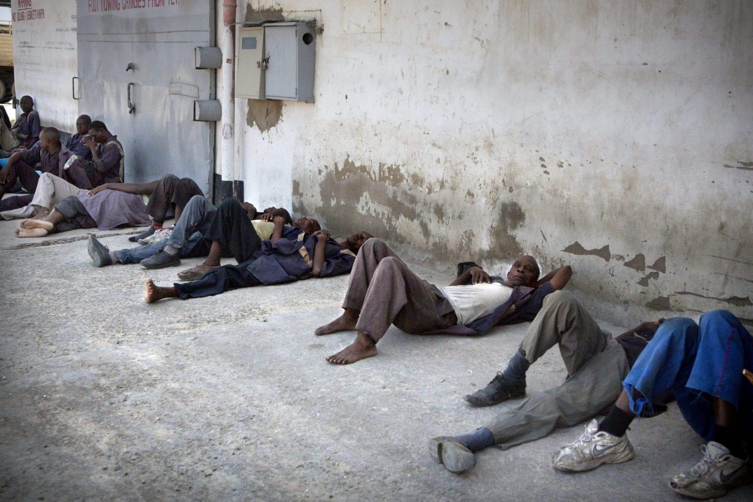 Bærere ligger og venter uden for et varehus. De ved ikke hvornår, men de ved, at der på et tidspunkt i løbet af dagen vil komme lastbiler, der skal tømmes. Foto: Linda Bournane Engelberth