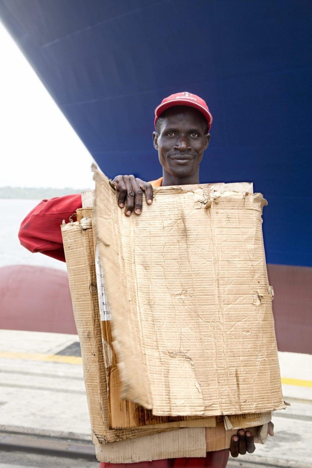 """""""Vi har vores senge herude. De der karton-ting – afrikanske senge"""", forklarer arbejdere, der er i færd med at laste et Mærsk-skib. De griner, mens en henter et par usamlede papkasser, og viser, hvad en """"afrikansk seng"""" er. Foto: Linda Bournane Engelberth"""