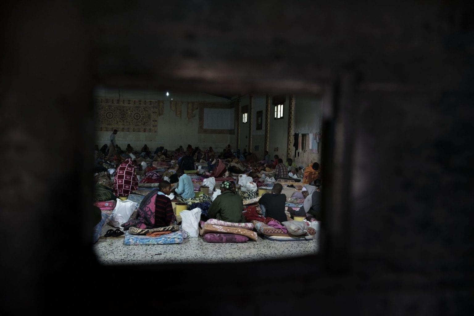 Set gennem en jerndør - her sidder migranter på madrasser i et fængsel i Libyen. Foto: UNICEF