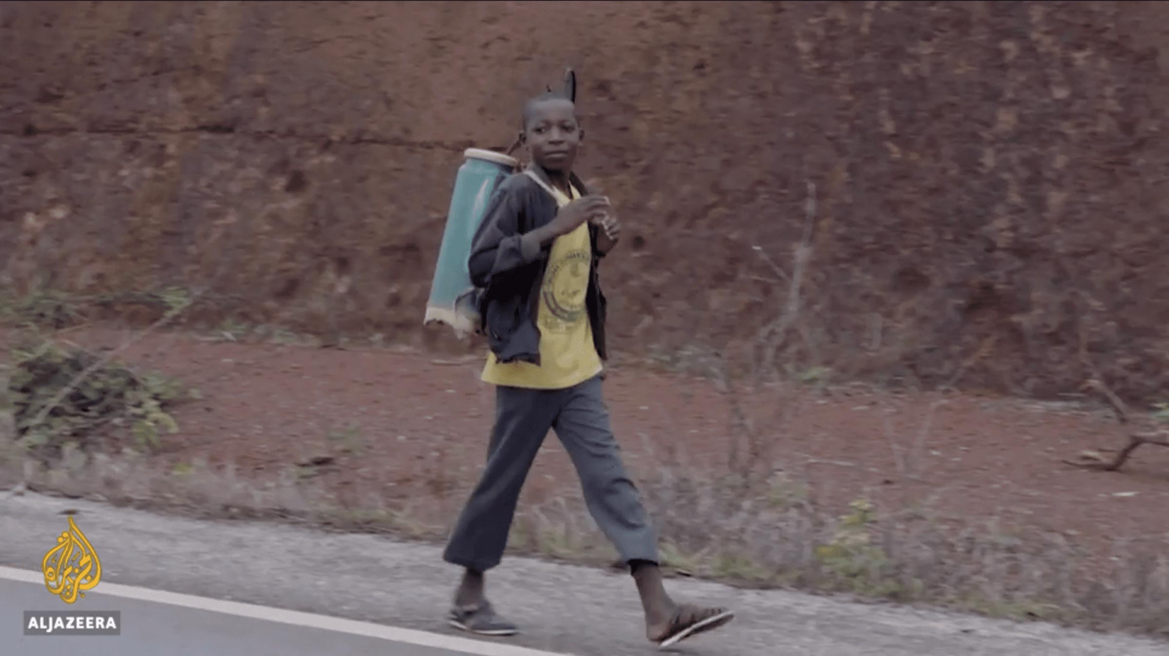 Et barn er på vej ud og sprøjte med farlige pesticider i en kakaoplantage i Elfenbenskysten.