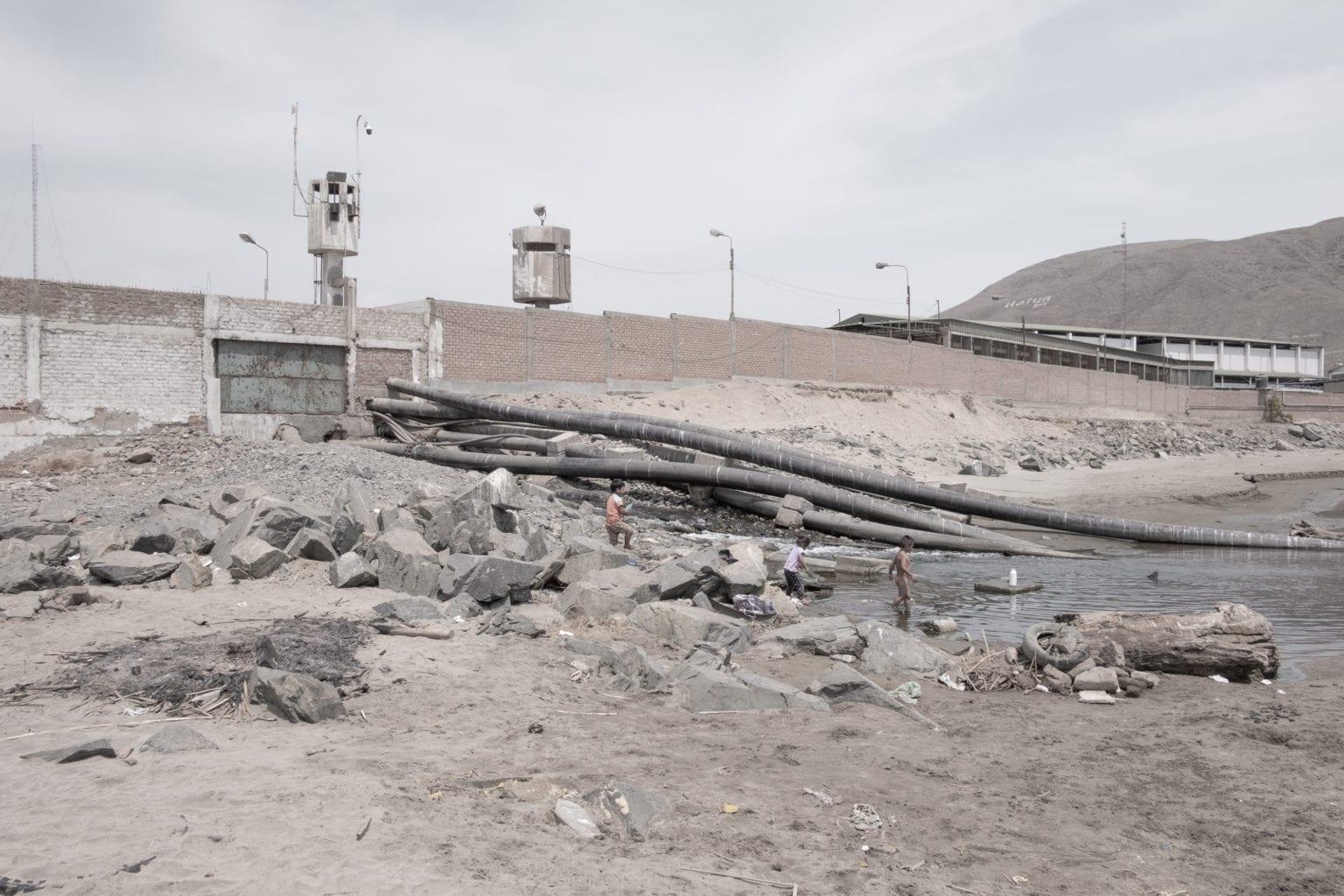 Tre børn leger på rørene fra fiskemelsfabrikken Pesquera Hayduk. Der er rør til at suge fisk ud af skibene, til at hente havvand op, som bruges i behandlingen af fiskene og til at slippe af med spildevand fra fabrikkerne.