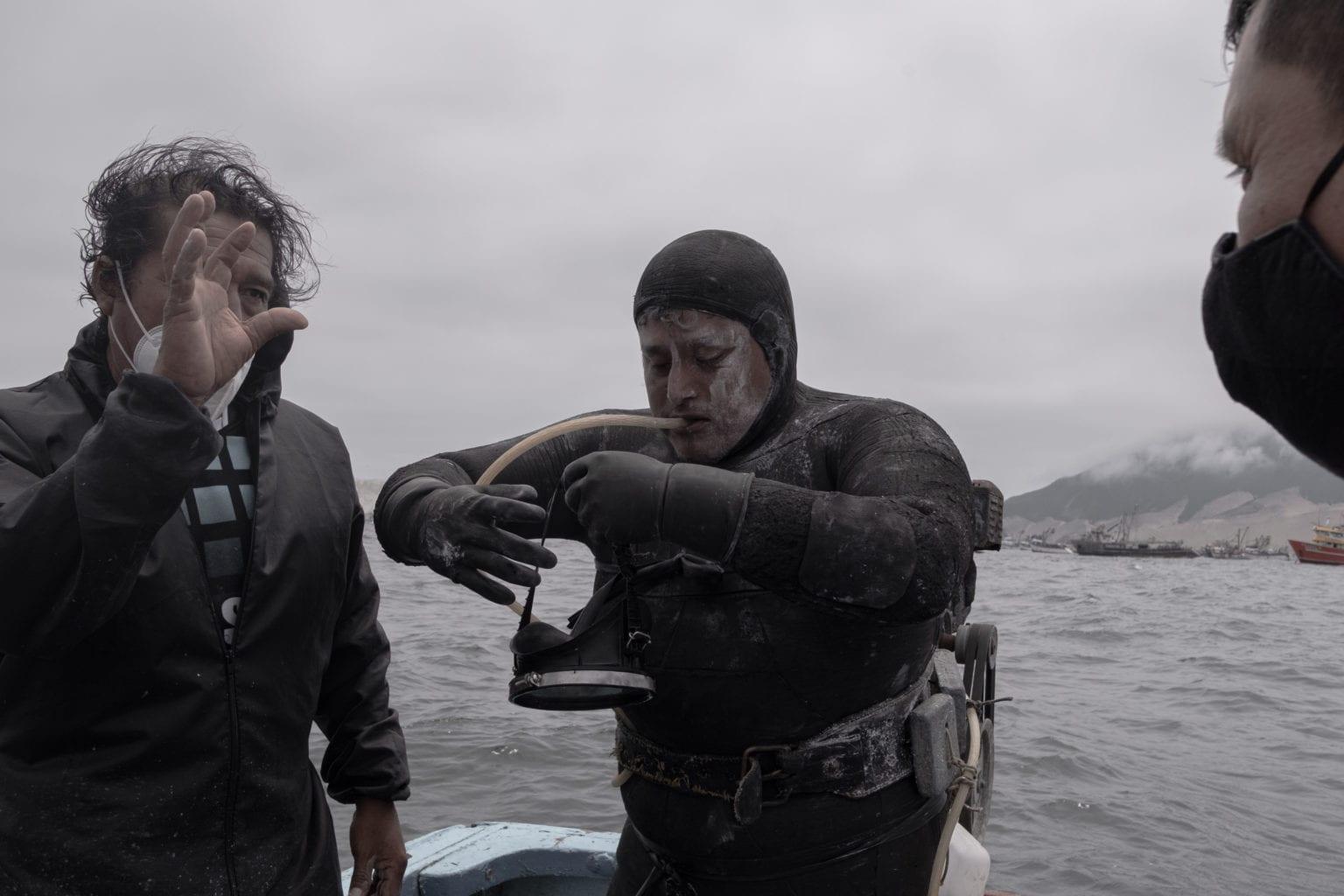 Det er dirty business at være dykker i Chimbote-bugten. Her er Diego Moya Salas ved at gøre sig klar til at hoppe i vandet. Han har snavs i ansigtet fra våddragten, der ikke er til at få ren efter en tur i bugten.