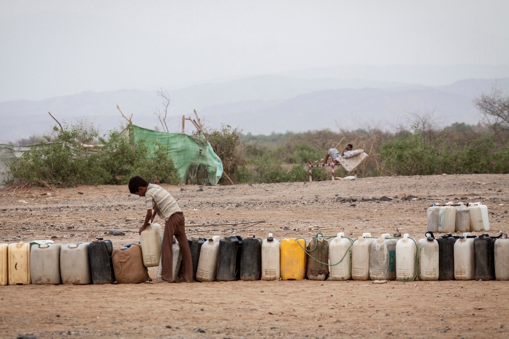 Containers are seen queueing as a displaced child from the heavy fighting in Haradh bordertown await for water distribution in a temporary settlement at the outskirts of Beni Hassan in Hajjah province, Northwest of Yemen.