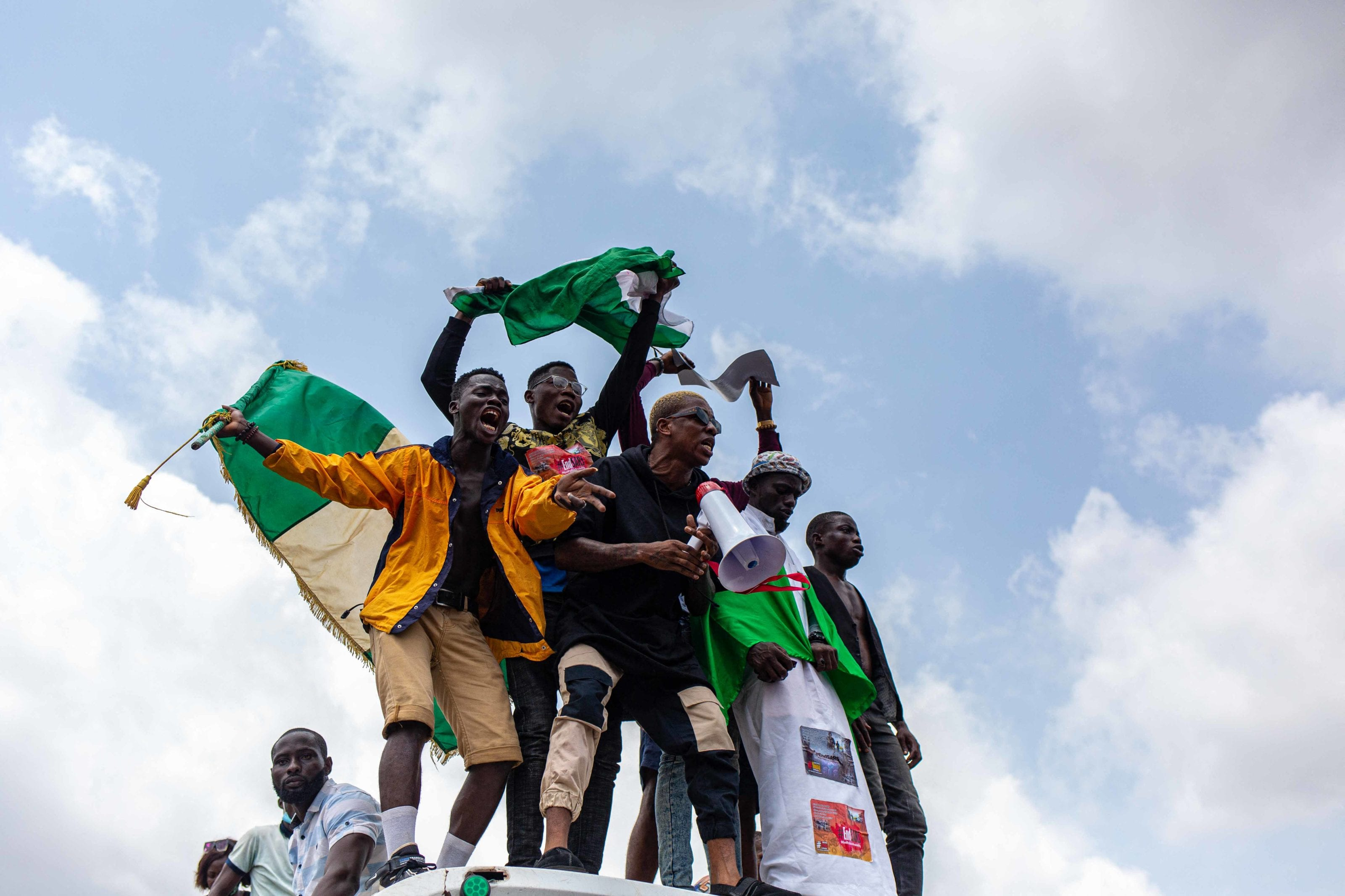 Nigerian youths seen waving the Nigerian national flag in front of a crowd in support of the ongoing protest against the unjust brutality of The Nigerian Police Force Unit named Special Anti-Robbery Squad (SARS) in Lagos on October 13, 2020. Nigerians took to the streets once again on October 13, 2020, in several cities for fresh protests against police brutality, bringing key roads to a standstill in economic hub Lagos.  Demonstrations organised on social media erupted earlier this month calling for the abolition of a notorious police unit accused of unlawful arrests, torture and extra-judicial killings. The government gave in to the demand on October 11, 2020, announcing that the federal Special Anti-Robbery Squad (SARS) was being disbanded in a rare concession to people power in Africa's most populous nation. Benson Ibeabuchi / AFP